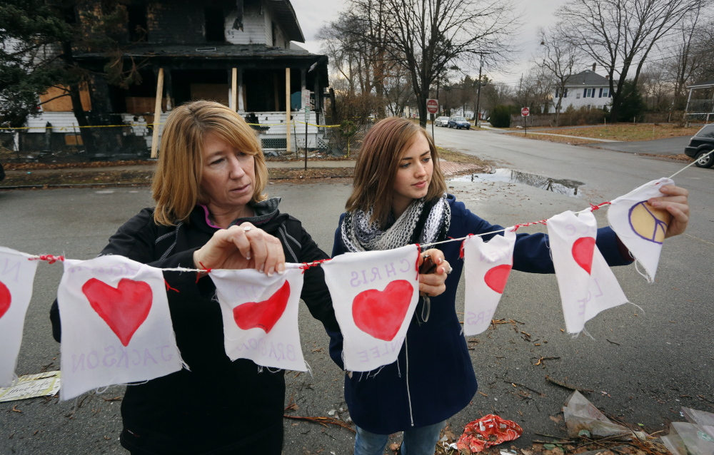 Catherine Wilson, left, and Grace Damon examine items left at a memorial across the street from the remains of a Noyes Street duplex that burned Nov. 1, killing six people. Wilson and Damon are organizing a group to defend the rights of Portland tenants.