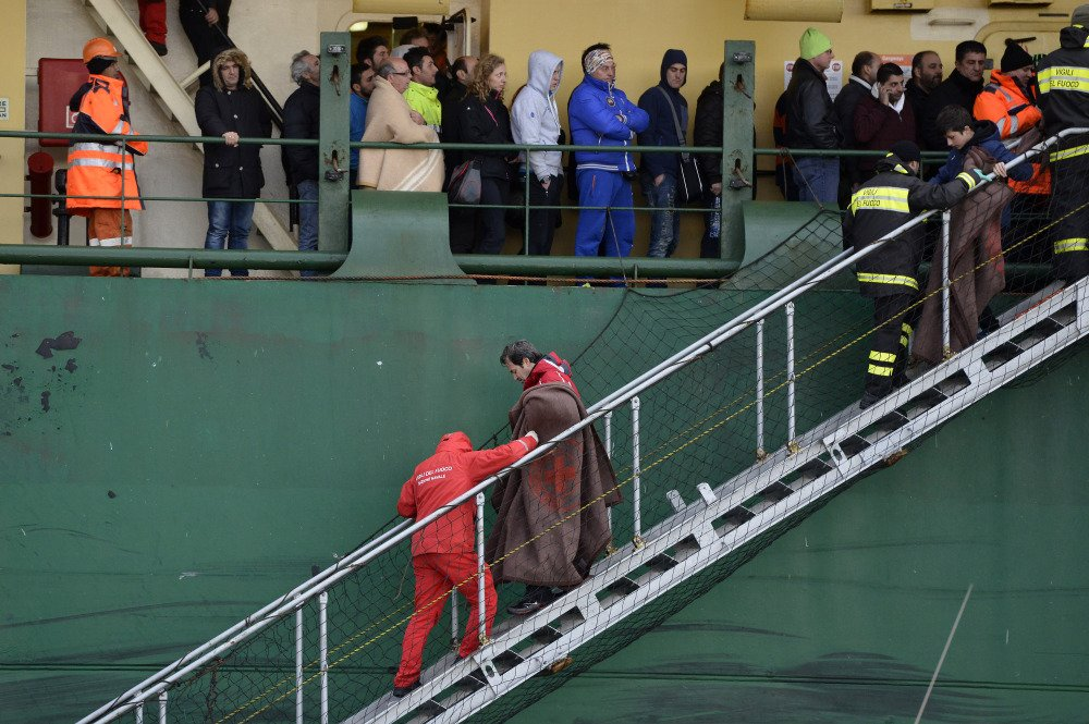 Passengers and crew members of the Norman Atlantic, which caught fire in the Adriatic Sea, disembark from a ship in southern Italy on Monday.