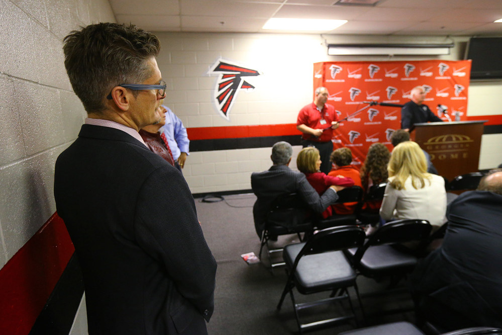Atlanta Falcons general manager Thomas Dimitroff, left, listens to coach Mike Smith during a news conference after the Carolina Panthers defeated the Falcons 34-3 Sunday in Atlanta.