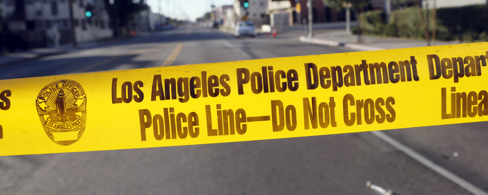 Crime scene tape stretches across a street in South Central Los Angles on Monday after police officers were shot at on Sunday. The area is plagued by gang violence.