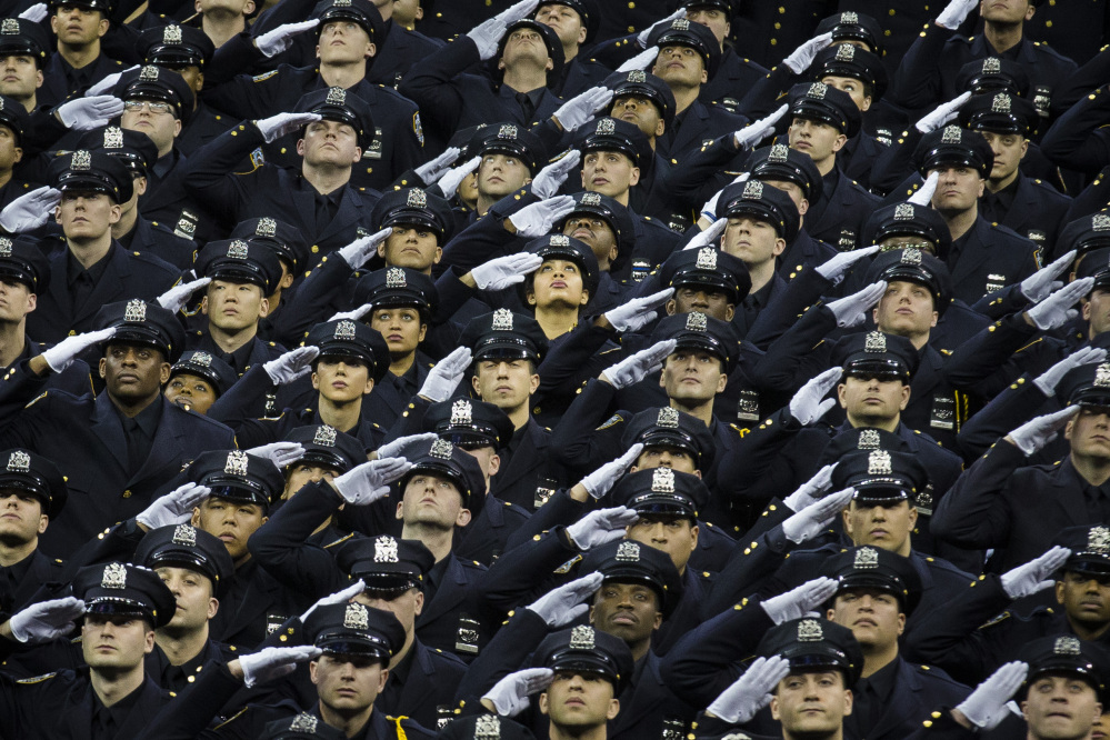 New officers salute their deceased comrades Rafael Ramos and Wenjian Liu during a New York Police Academy graduation ceremony on Monday. Nearly 900 officers were sworn in amid boos and heckles at New York's mayor.