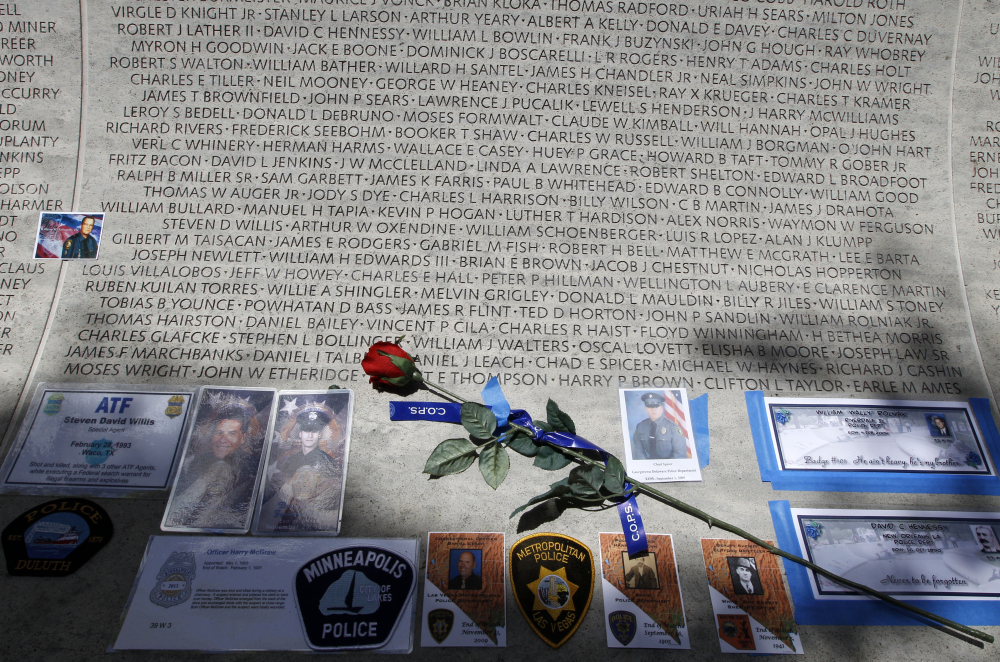 A rose is placed at the wall with the names of fallen police officers at the National Law Enforcement Officers Memorial in Washington during National Police Week in May.