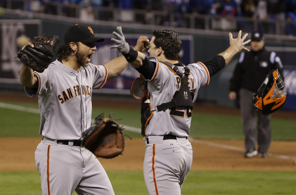 In this Oct. 29 file photo, San Francisco Giants pitcher Madison Bumgarner, left, and Buster Posey celebrate after winning 3-2 to win the series over Kansas City Royals after Game 7 of baseball's World Series in Kansas City, Mo.