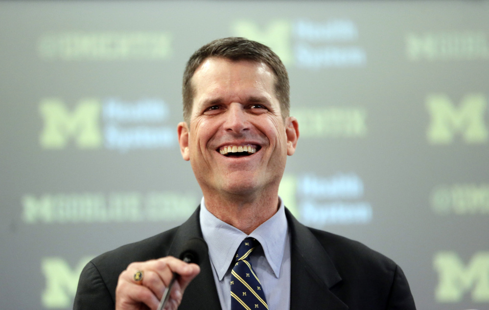 Jim Harbaugh, Michigan's new head football coach, addresses the media after after he was introduced during an NCAA college football news conference Tuesday, in Ann Arbor, Mich.