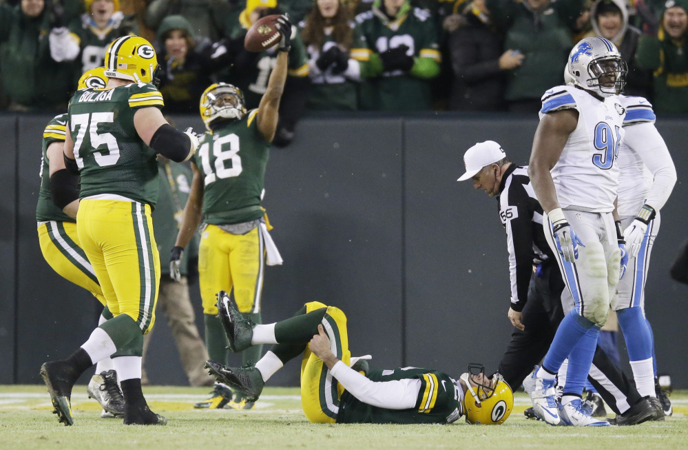 Packers quarterback Aaron Rodgers holds his leg as Randall Cobb celebrates a touchdown catch during the first half of Sunday's game against the Detroit Lions. Rodgers left the game on a cart, but returned to play in the second half of Green Bay's win.