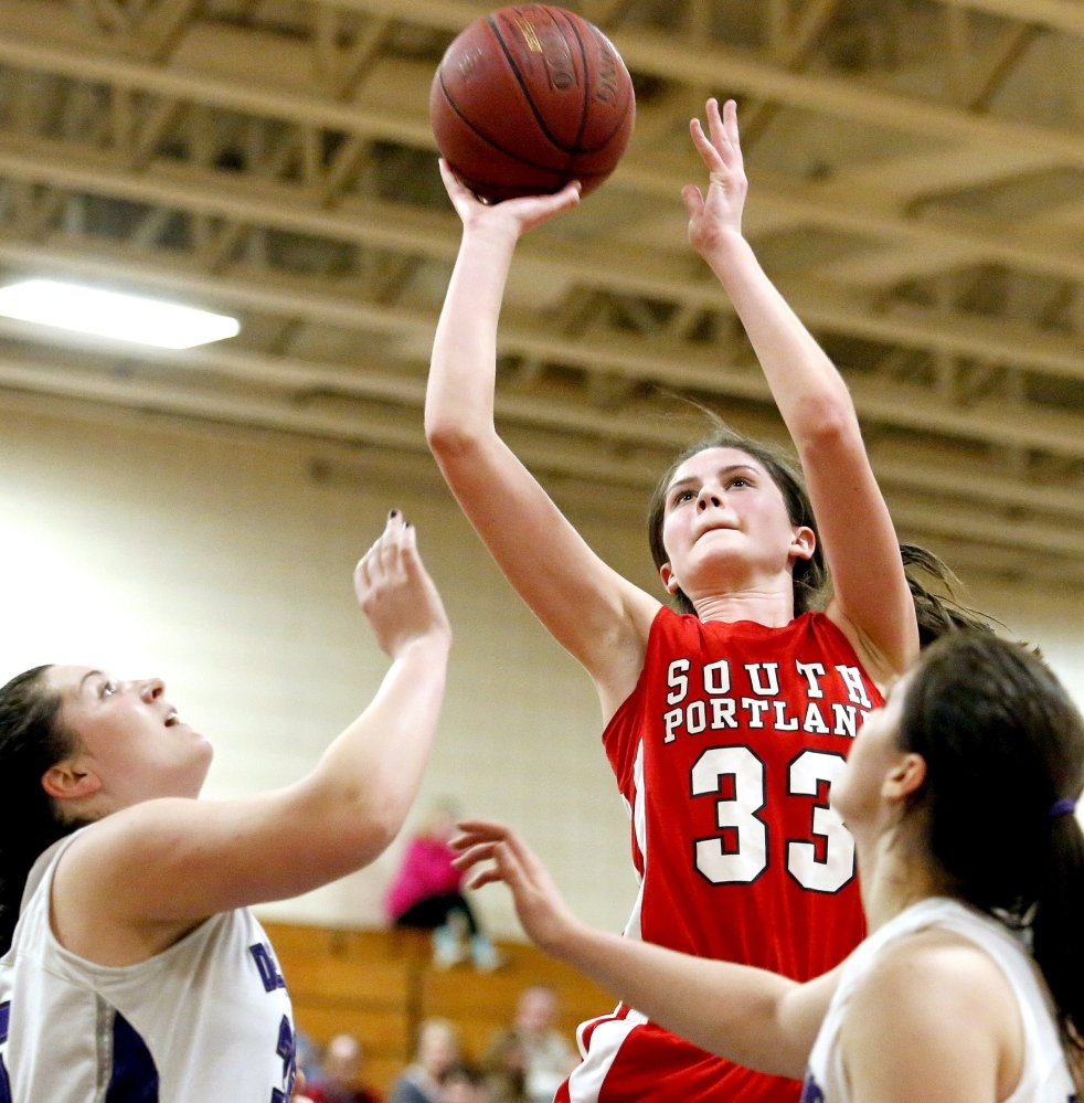 South Portland's Maddie Hasson takes a shot over Amanda Brett and Cierra Burnham of Deering in Tuesday night's SMAA girls' basketball game at Portland. Deering rallied for a 59-52 win in overtime.