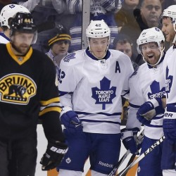 Toronto's Phil Kessel (81) celebrates his goal with teammates Tyler Bozak (42) and Cody Franson (4) as the Bruins' Dennis Seidenberg skates away during the second period of Wednesday night's game in Boston. The Bruins tied the game with two goals late in the second period, but lost in an overtime shootout.