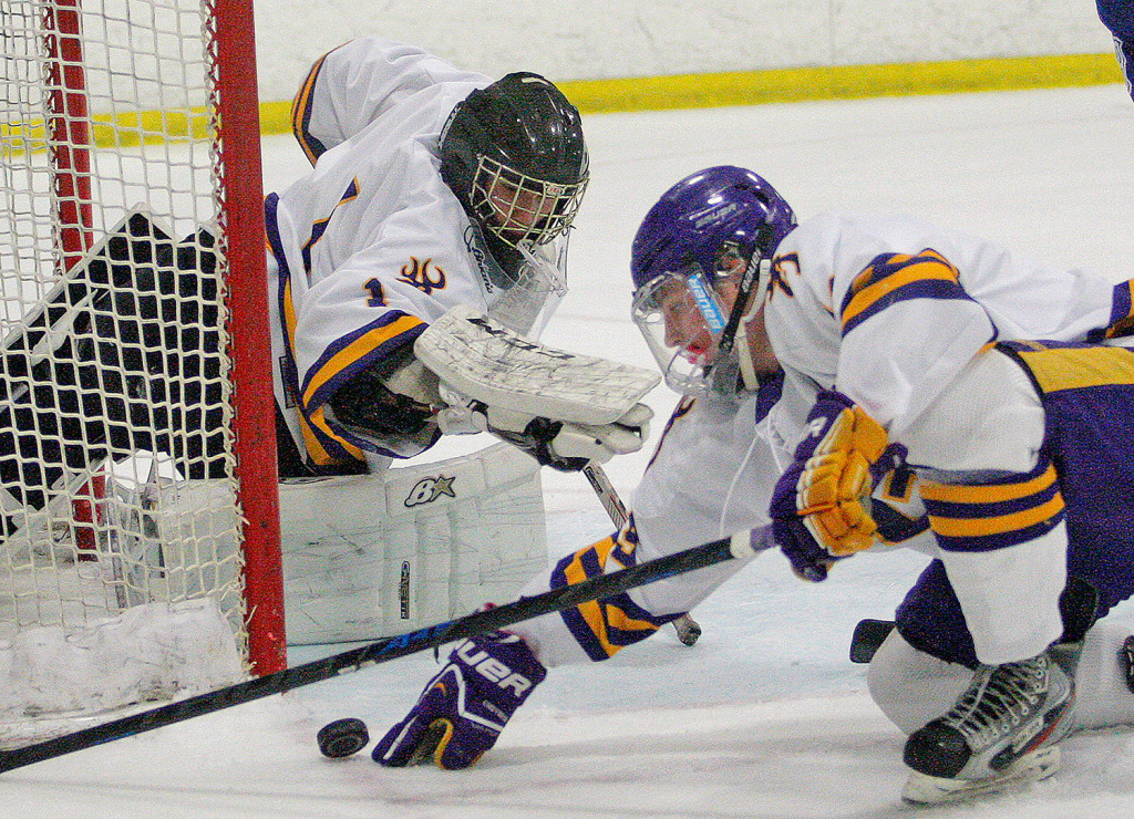 Cheverus goalie Kyle Severance and captain James Kane try to keep the puck from going in the goal during a game against Lewiston at the Portland Ice Arena on Dec. 6. The Stags won, 3-2.