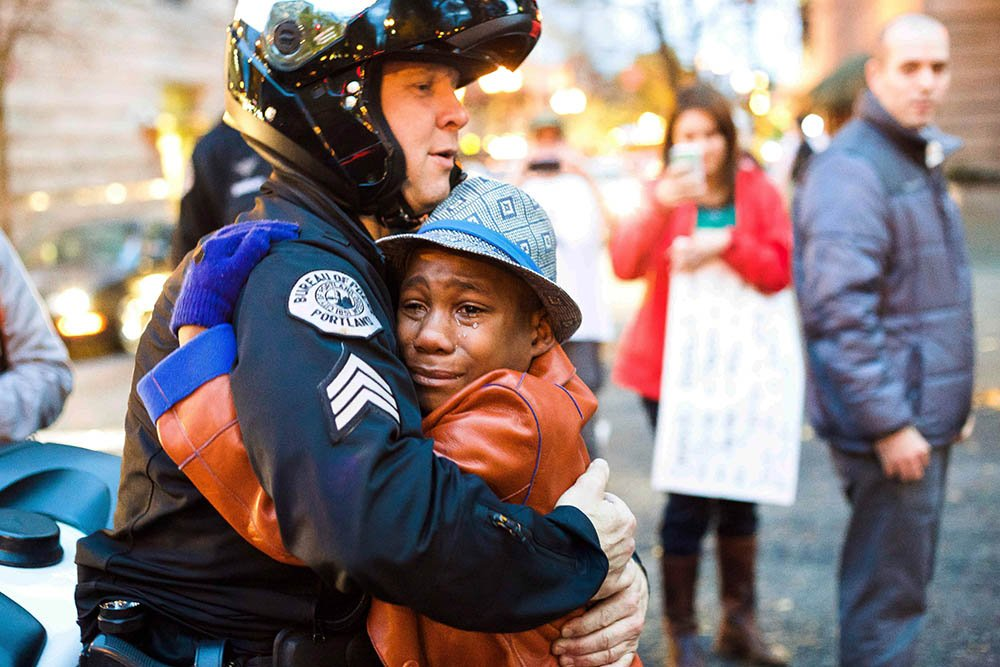 Police Sgt. Bret Barnum and Devonte Hart, 12, hug at a rally in Portland, Ore., where people had gathered in support of the protests in Ferguson, Mo., on Nov. 25.