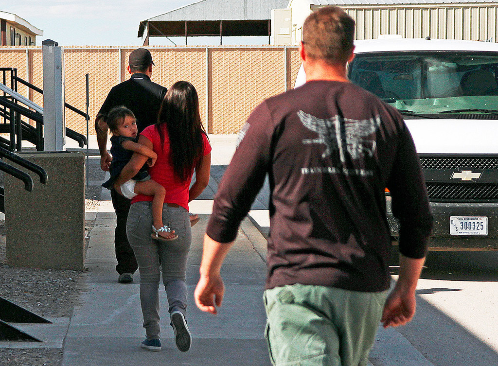 A woman and child are escorted to a van by detention facility guards inside the Artesia Family Residential Center, a federal detention facility for undocumented immigrant mothers and children in Artesia, N.M.
