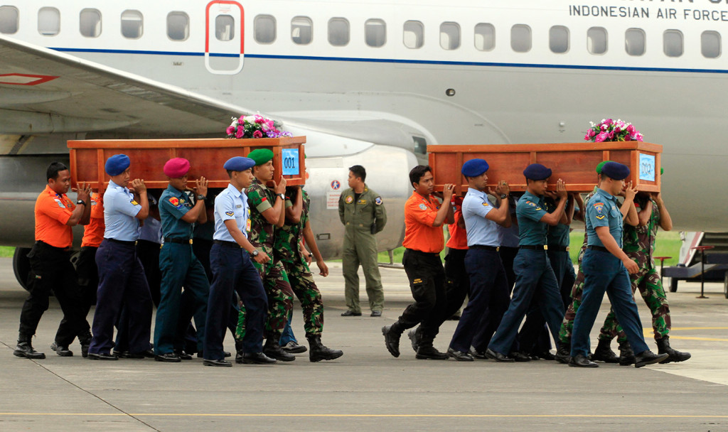Indonesian soldiers carry coffins containing bodies of victims of AirAsia Flight 8501 upon arrival at  Indonesian Military Air Force base in Surabaya, Indonesia, Wednesday. A massive hunt for the victims of the jet resumed in the Java Sea on Wednesday, but wind, strong currents and high surf hampered recovery efforts as distraught family members anxiously waited to identify their loved ones. The Associated Press