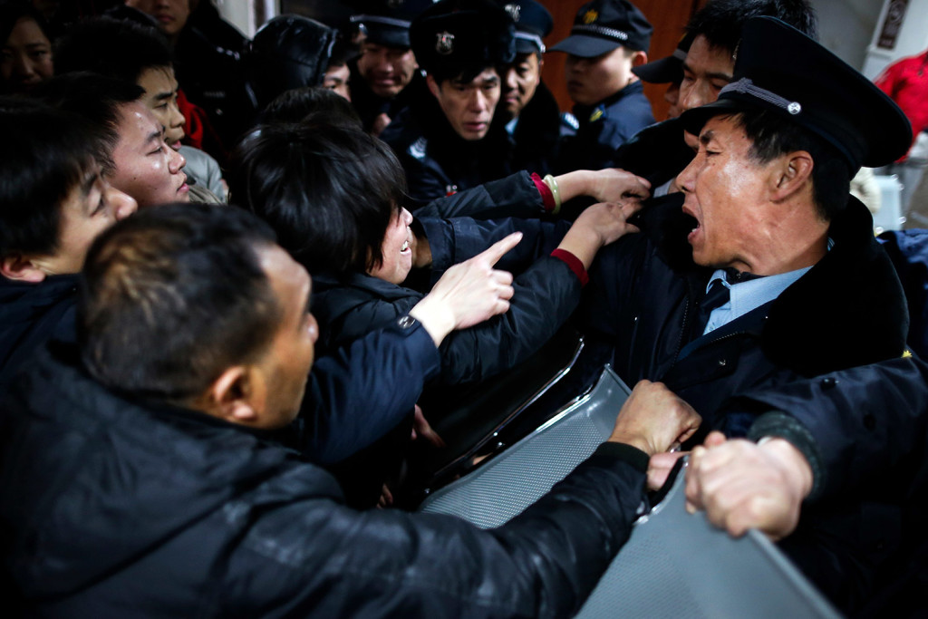 Relatives of people injured in a stampede in Shanghai, China, on Thursday try to push past security guards at a hospital where victims were being treated.