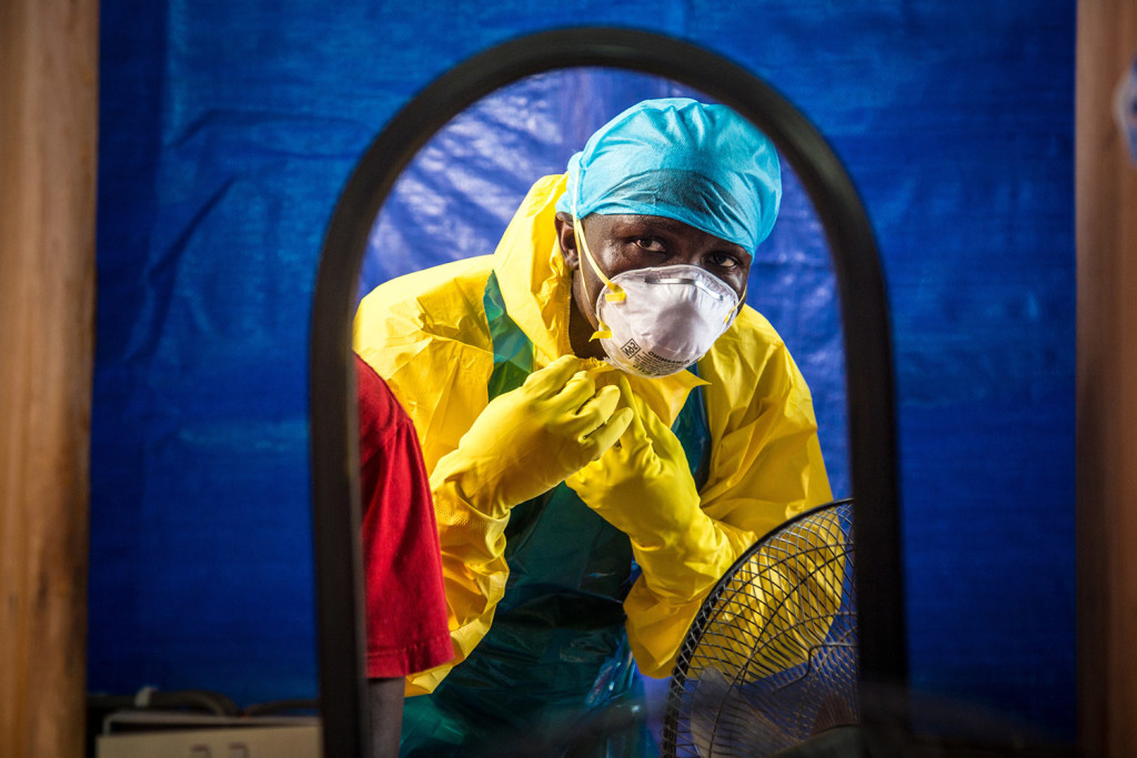 A health care worker dons protective gear before entering an Ebola treatment center in Freetown, Sierra Leone, in October. In a letter published online Wednesday by the New England Journal of Medicine, doctors report that the Ebola death rate appears to have fallen, even though there are no specific medicines or vaccines to fight the virus.