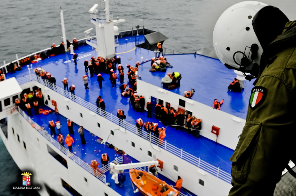 Passengers and crew wait on the Norman Atlantic's deck as a rescue helicopter and multiple vessels respond to the emergency. Gale-force winds and massive waves further hampered rescue efforts, which continued into Sunday night. The Associated Press