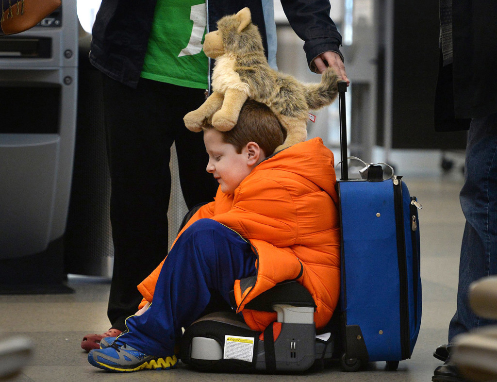 "David Welborn, 7, sits in the lost luggage line at the Delta Airlines desk at RDU International Airport on Tuesday  With his trusty dog ""Wolfbaby"" perched on his head, he was with his mother and about 15 other people trying to find their bags after a  flight from Washington state. The Associated Press"