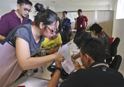 Relatives of the passengers onboard AirAsia flight QZ8501 check the plane's manifest at a crisis center set up at Juanda International Airport in Surabaya, East Java, Indonesia, on Sunday. The Associated Press