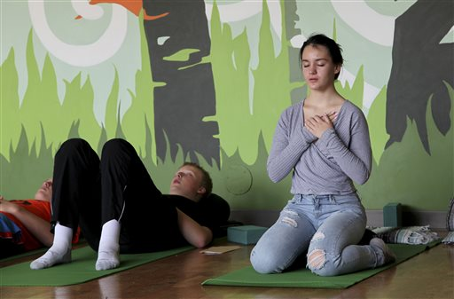 Nora Pearson, right, practices mindful breathing during the Mindful Studies class at Wilson High School in Portland, Ore. The Associated Press