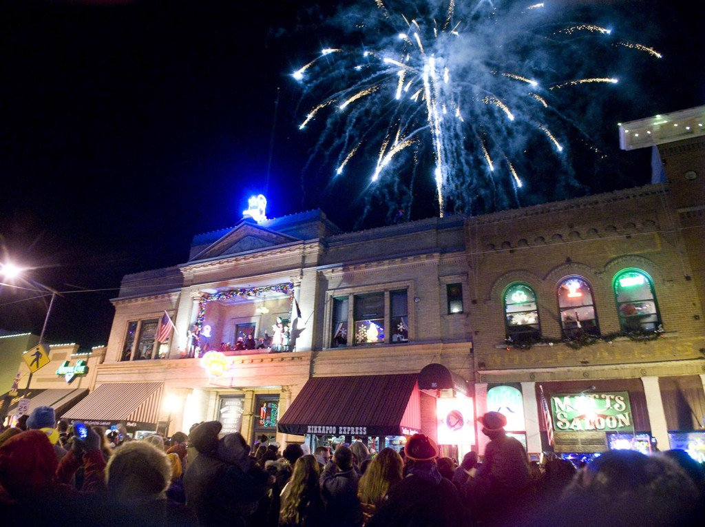 In this Dec. 31, 2013 photo, the crowd cheers and fireworks explode in the sky as a lighted cowboy boot drops to the roof of the Palace Saloon New Year's Eve on Whiskey Row in downtown Prescott, Ariz.