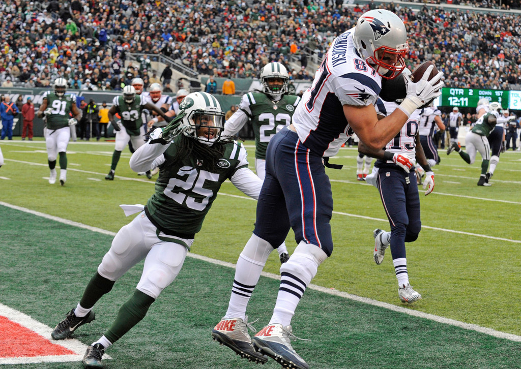New England Patriots tight end Rob Gronkowski scores a touchdown as New York Jets' Calvin Pryor (25) closes in during the first half of Sunday's game in East Rutherford, N.J.