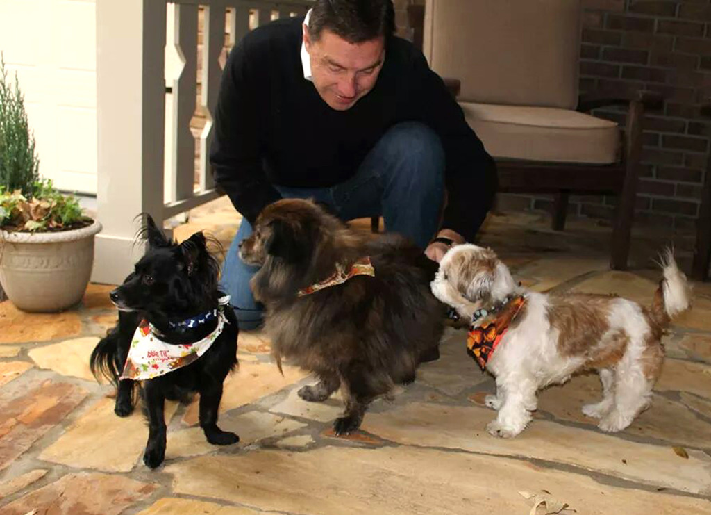 n this Nov. 23, 2014 photo provided by Jan Trantham, Will Trantham kneels by Jackson, left, a Shih Tzu, along with Darcy, center, and Sophie. The Associated Press
