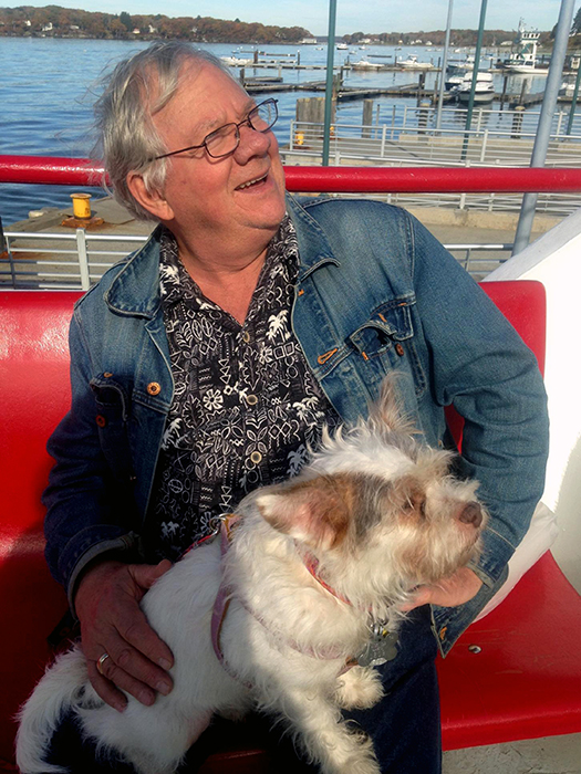 In this undated photo provided by Caren Ferris, John Ferris rides with his adopted dog Ginger on a ferry to Peaks Island, Maine. Ferris, from Amherst, Mass., with his wife, adopted Ginger from the Aloft Hotel in downtown Asheville, N.C., where the couple were staying nearby when they met the 4-year-old terrier mix in the hotel bar sporting an