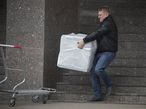 A man carries a dishwasher he purchased in St.Petersburg, Russia, Wednesday. The collapse of the national currency triggered a spending spree by Russians desperate to buy cars and home appliances before prices shoot higher. The Associated Press