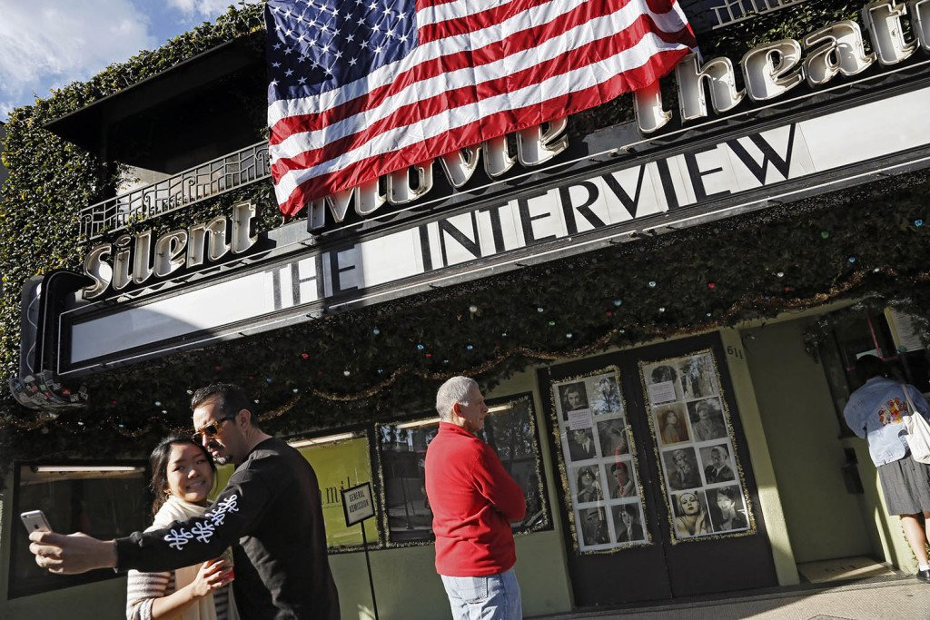 "Bernard Denney takes a selfie with his girlfriend Maho Tanaka, left, in front of the Cinefamily at Silent Movie Theater in Los Angeles on Thursday prior to attending the movie ""The Interview."""