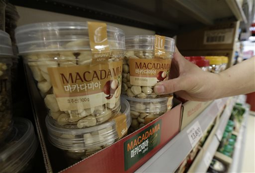 A customer picks up a plastic container of Macadamia nuts at a store in Seoul, South Korea, Monday. The Associated Press