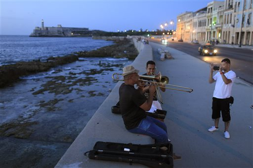 Musicians perform as a tourist from Colombia takes their picture along the Malecon in Havana, Cuba, in this July 8, 2013, photo.