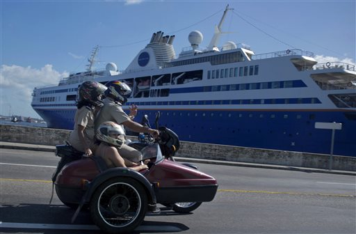 A trio of people ride a motorcycle with sidecar past the Semester at Sea cruise ship docked in Havana's harbor In this Dec. 9, 2013, photo. The Associated Press