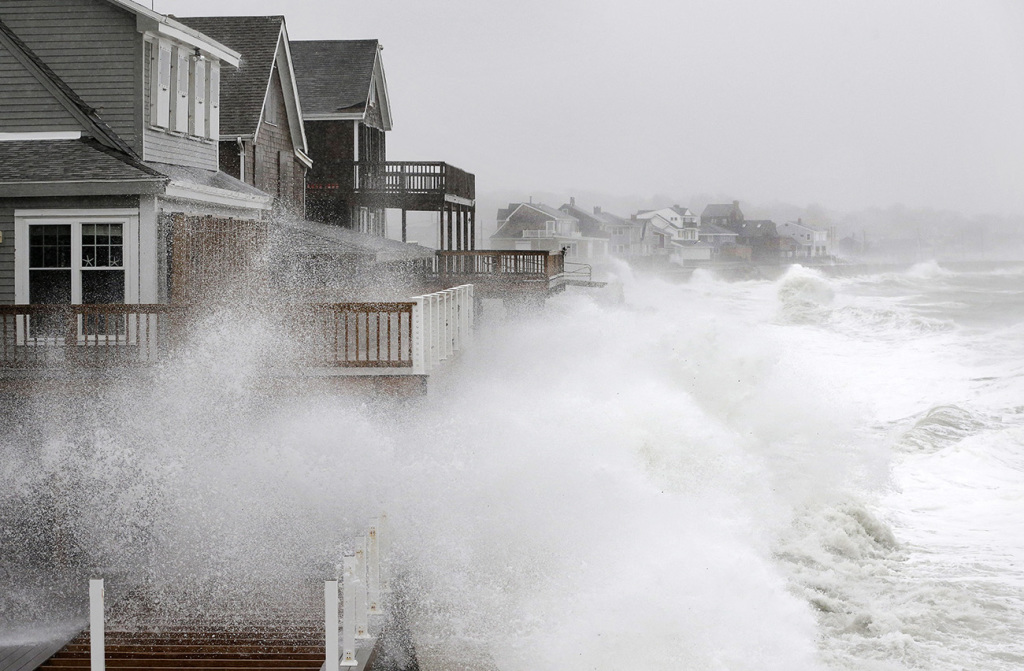 Waves splash against a seawall and onto houses along the Atlantic Coast on Tuesday in Scituate, Mass. The National Weather Service posted a flood watch for urban and poor drainage areas, and a coastal flood advisory for the midday high tide cycle.