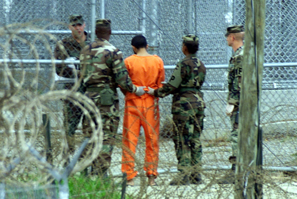 "Military police on the Naval Base at Guantanamo Bay bring a detainee back to his cell after an interrogation session in this Feb. 6, 2002, photo. The methods used to interrogate detainees ""regularly resulted in fabricated information,"" the Senate report concludes. Reuters"