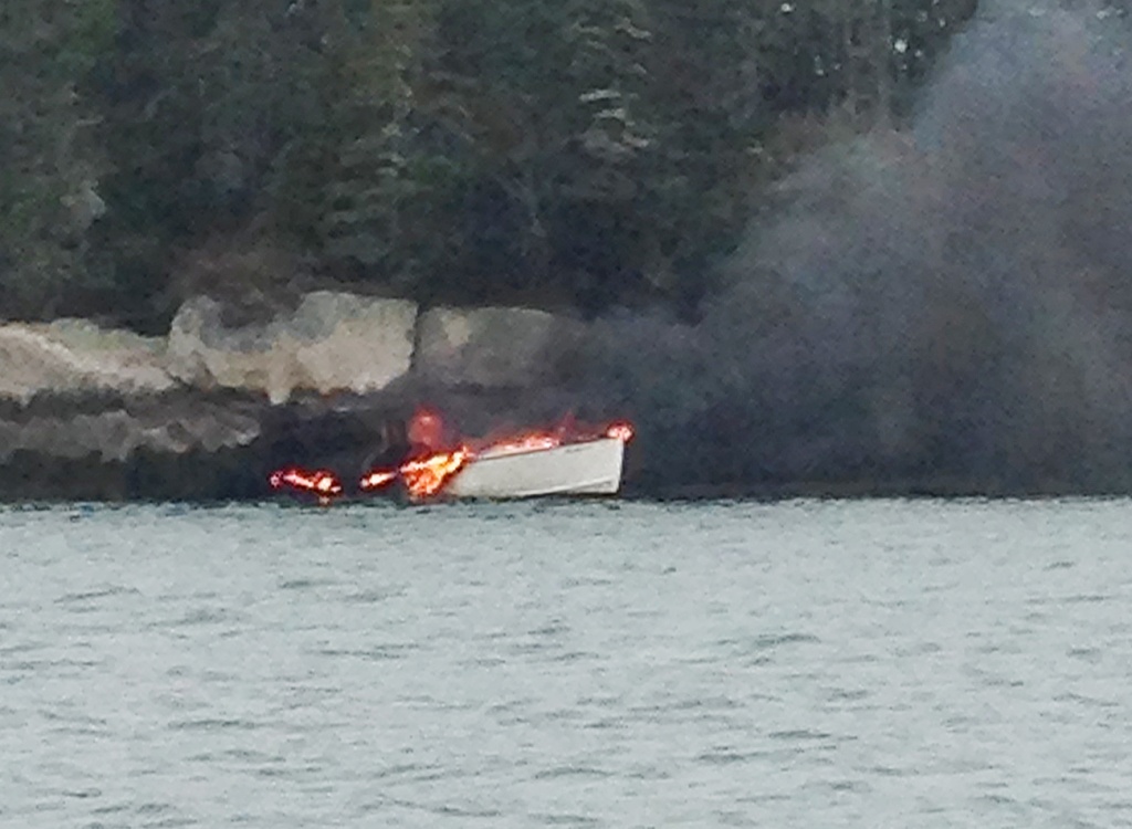 The Midnight Rider, a 25-foot inboard lobster boat, burns near Crane Island on Tuesday where it drifted after David and Blake Anthony jumped overboard and swam to nearby Cedar Island and safety. Maine Marine Patrol photo by Officer Brandon Bezio