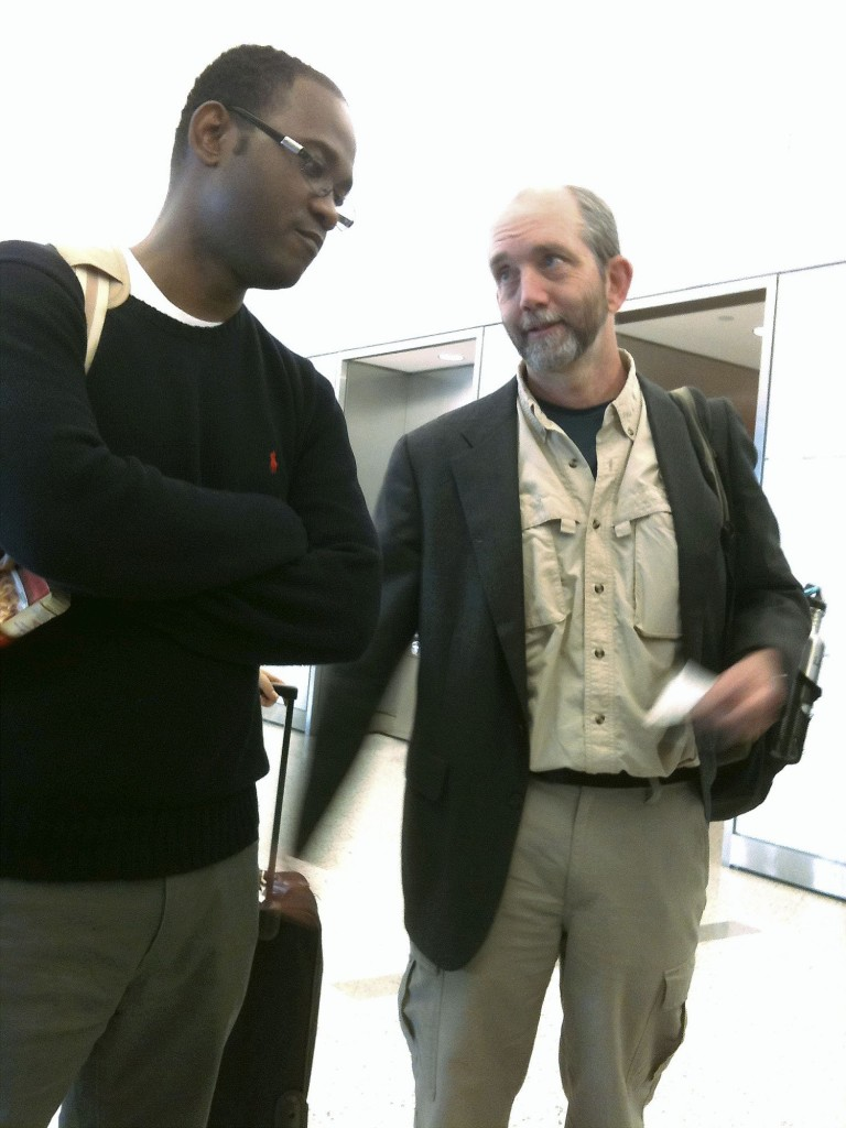 Nate Nickerson, right, executive director of Konbit Sante, talks with Lionel Maledranche at New York's Kennedy Airport on Saturday. Maledranche, a New Jersey doctor, was returning to Haiti to check on his family. Nickerson is trying to reach Cap-Haitien, Haiti's second-largest city.