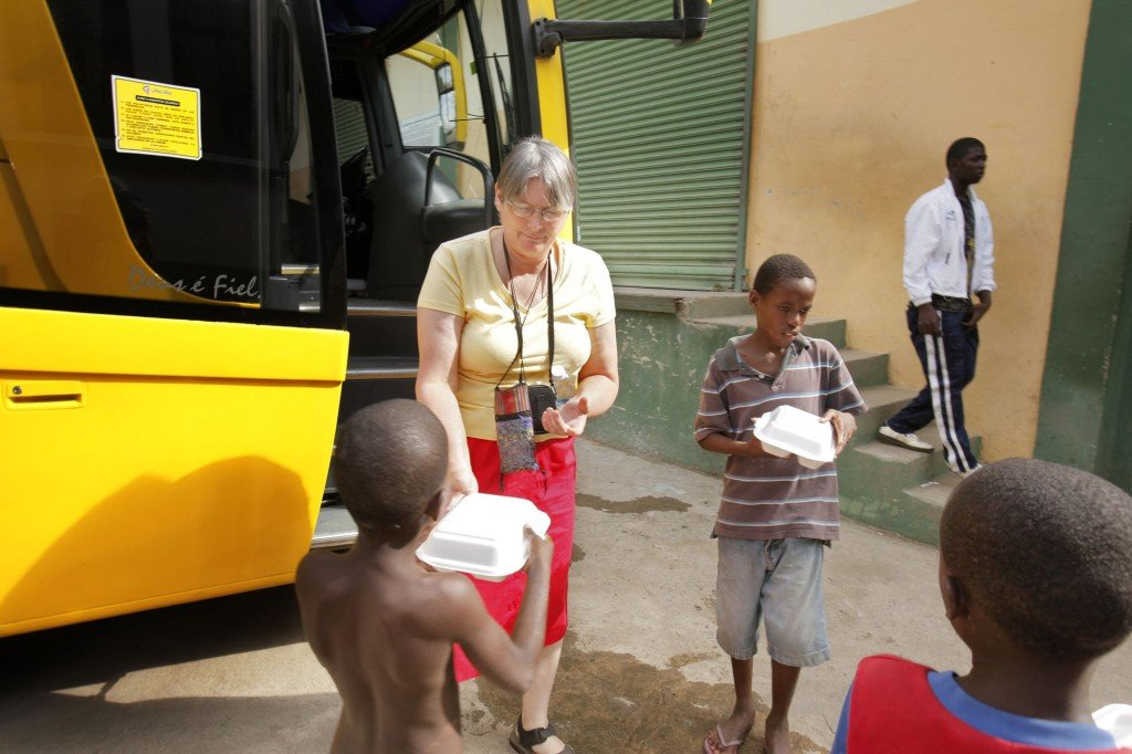 Terry Johnston of Jefferson hands a lunch to a boy in the border town of Dajabon in the Dominican Republic on Sunday. She had received the food on her bus trip to Cap-Haitien, in northern Haiti. Johnston has been visiting Terrier Rouge, a nearby town, since 2002 and has set up a network through her church to help the town's residents.
