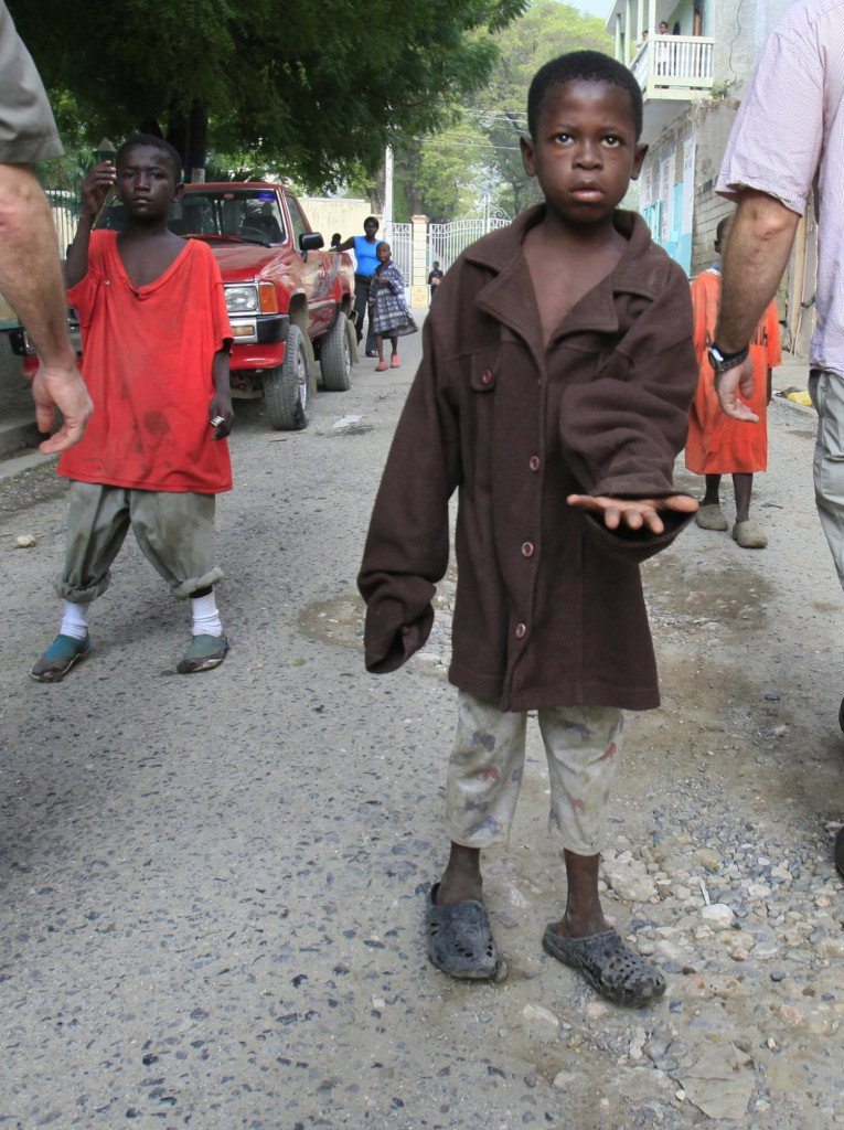 A boy asks for money as foreign visitors walk past him on a street in Cap Haitien, Haiti.