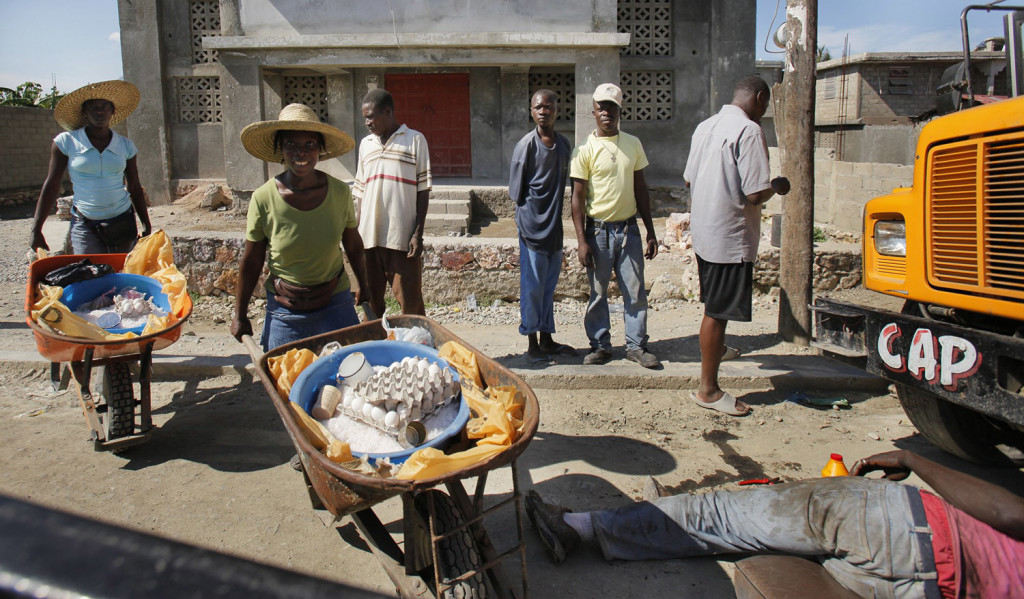 A man works under a bus while two women pushing wheelbarrows of goods wait to pass in Cap Haitien.