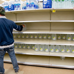 A shopper grabs a gallon of water at the Hannaford supermarket on Forest Avenue in Portland on Monday, the day before the blizzard hit. Bottled water is the top item to fly off Hannaford stores' shelves before a big storm.