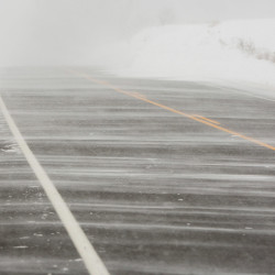 Gusting wind blows snow across an empty Route 5 in Dayton.