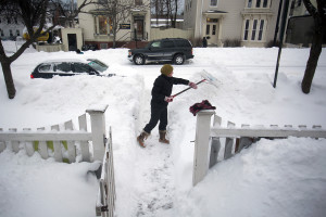 Elizabeth Fraser digs a tunnel from her front door to the street in waist high snow drifts after a blizzard hit Maine Wednesday. Gabe Souza/Staff Photographer