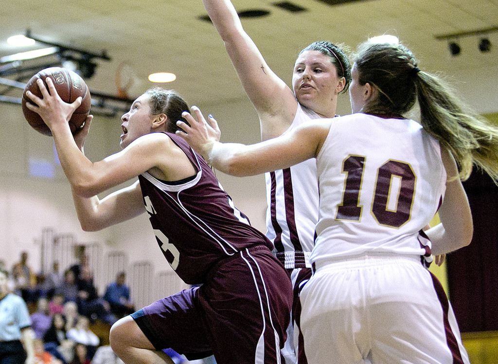 Gorham's Emily Esposito ducks under Thornton Academy's Victoria Lux and Kaitlyn McCrum for a late-game basket during a girls basketball game, Monday in Saco. Gabe Souza / Staff Photographer