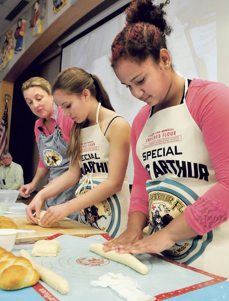 Skowhegan Area Middle School students Katelin Warren, center, and Shaneka Sapienza roll out fresh dough to make braided bread under the guidance of Amy Driscoll, of the King Arthur Flour Co., during a workshop at the school.
