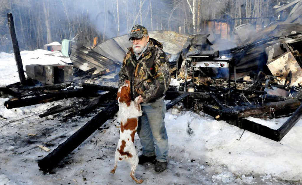 Herb Hingley's dog Babe jumps up on him beside his home that was destroyed by fire on Rowe Pond Road in Pleasant Ridge Plantation on Wednesday. Hingley credited his dog with alerting him to the early-morning fire.
