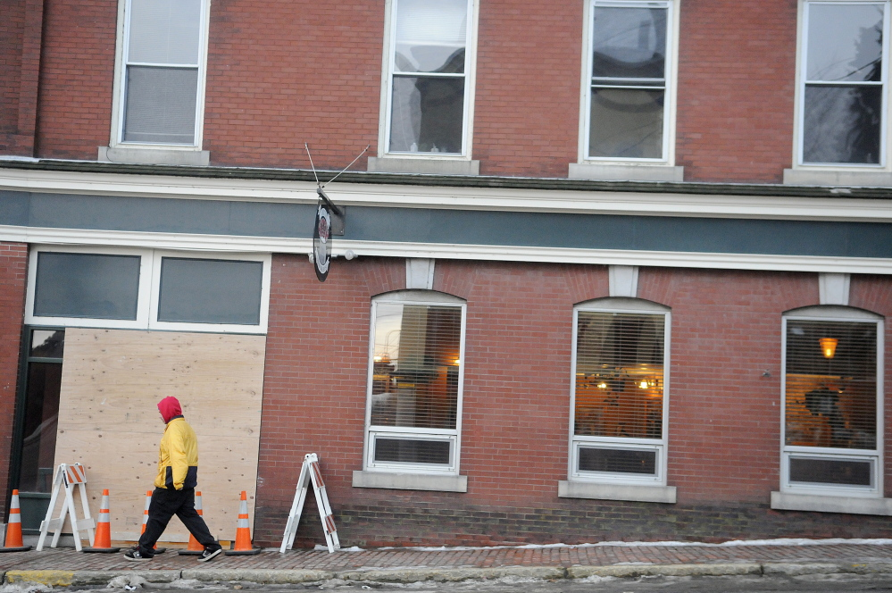 A man walks down Winthrop Street in Hallowell past the boarded up window at Hattie's Chowder House on Monday. Andy Molloy / Kennebec Journal Staff Photographer