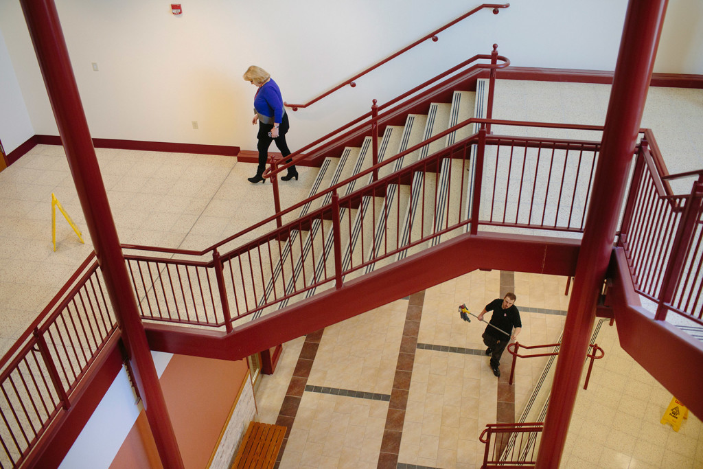 South Portland Superintendent Suzanne Godin walks down the stairs of the recently renovated South Portland High School on Friday while Aaron Bouchard mops the atrium. Godin spent Friday making sure all the furniture was in the right places.