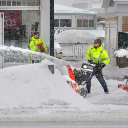 Matt Curtis blows snow from the sidewalk to the snow bank while his crew cleans up with shovels as the snow falls around them Friday. They all work for Curtis Lawn and Yard Care and have the contract to clean about a half mile of sidewalk in front of the Freeport outlets on Main Street.