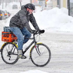 Chris Mills braves the heavy snow as he rides his bike, equipped with tires, along Main Street in Freeport on his way to work at the Bike, Boat and Ski retail store.