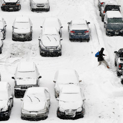 A man carefully steps over a snowbank in a snow-covered parking lot on Free Street in Portland during Friday's snowfall.
