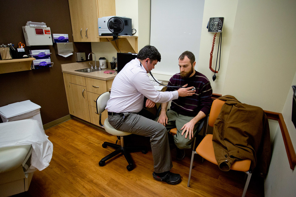 Dr. Brad Huot, a primary care physician at Martin's Point Health Care on Veranda Street in Portland, checks the heart rate of Tyson O'Keefe on Tuesday. The state announced that it will fill about an $8 million gap in federal funding to keep MaineCare reimbursements for physicians the same.