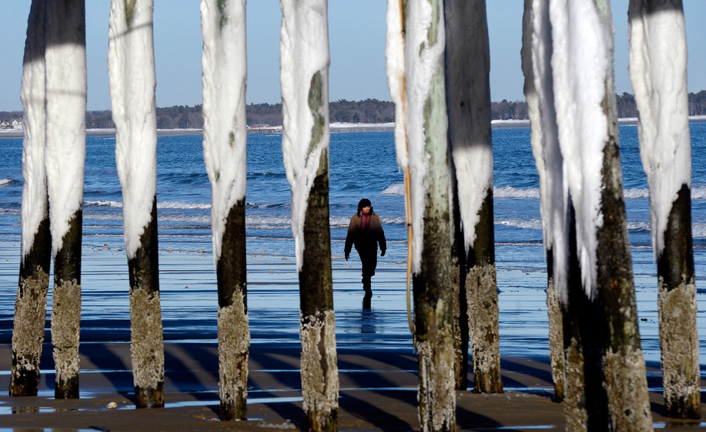 The pier's pillars in Old Orchard Beach are covered in snow and ice as Elisa Jacobs of Needham, Massachusetts, walks along the beach Thursday, two days after a blizzard and one day before Maine's next snowstorm.